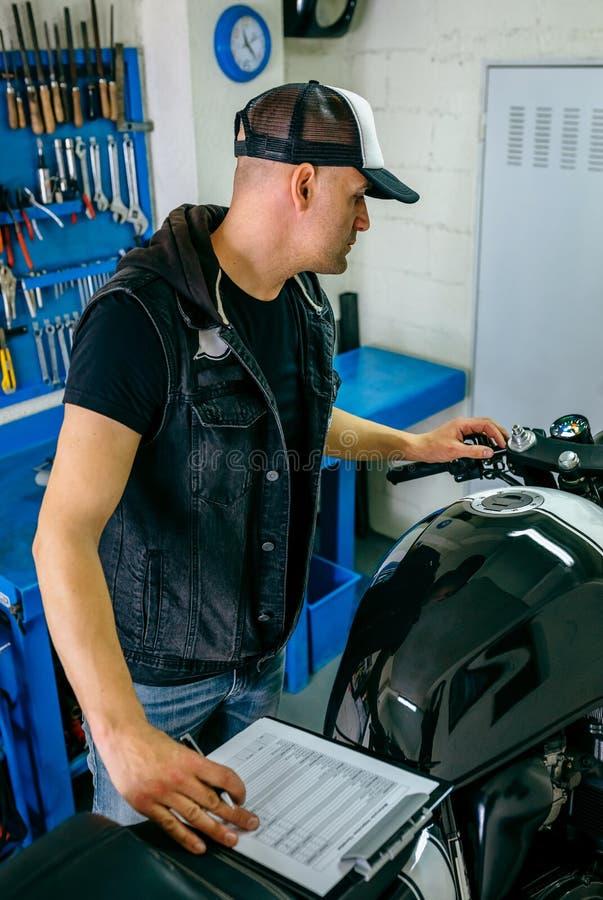 Mécanicien vérifiant la moto photographie stock libre de droits