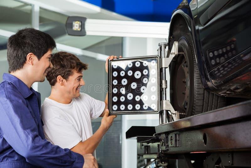 Mécanique ajustant le dispositif d'alignement de roue sur la voiture photo stock