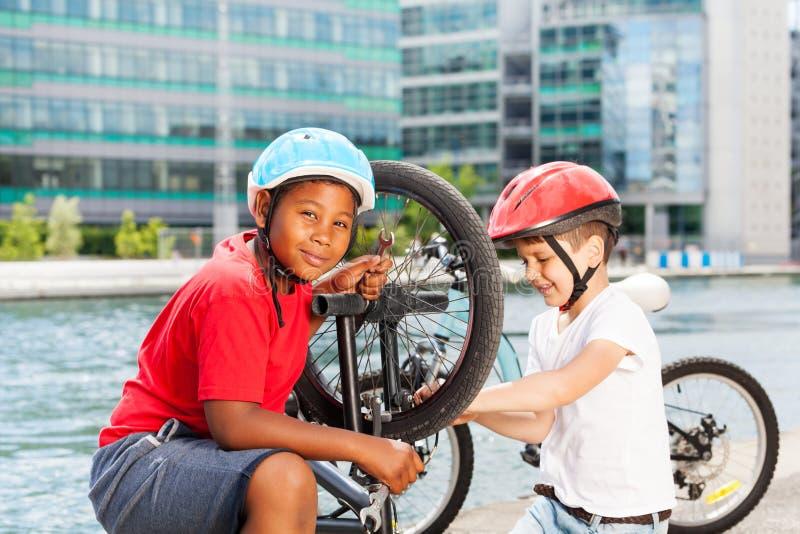 Mécanique d'enfants réparant la bicyclette dehors photos libres de droits