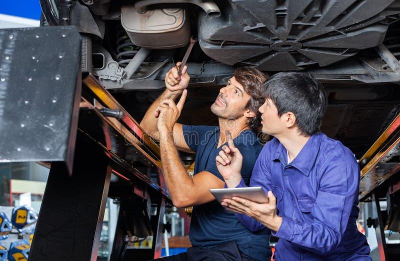 Mécanique discutant au-dessus de la Tablette de Digital sous la voiture soulevée images libres de droits