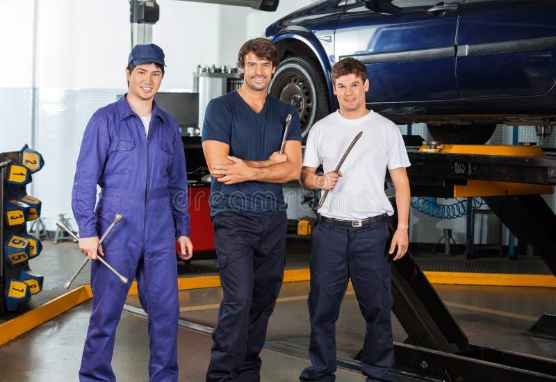 Mécanique sûre tenant Worktools au garage photo stock