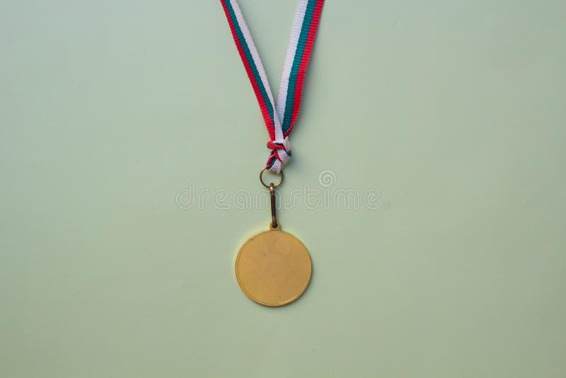 médaille d'or sur un ruban multicolore sur un fond vert photos stock