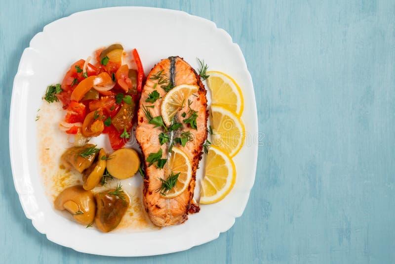 Médaillon saumoné cuit au four de filet avec de la salade des légumes et des champignons marinés d'un plat blanc sur un fond bleu photographie stock