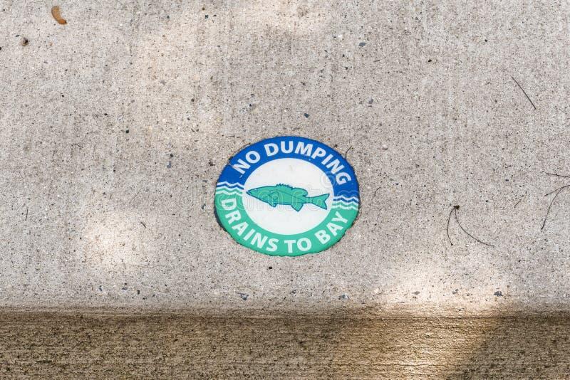 Médaillon vert avec un poisson dessus et les mots `Pas de déversement de drains vers la baie photos libres de droits