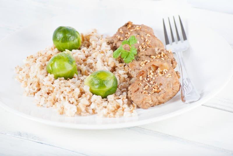Médaillons et riz brun avec des choux de bruxelles sur le blanc images stock