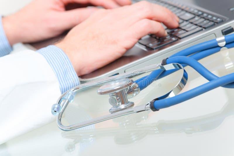 Médecin dactylographiant sur l'ordinateur portable images libres de droits