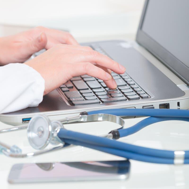 Médecin dactylographiant sur l'ordinateur portable image libre de droits