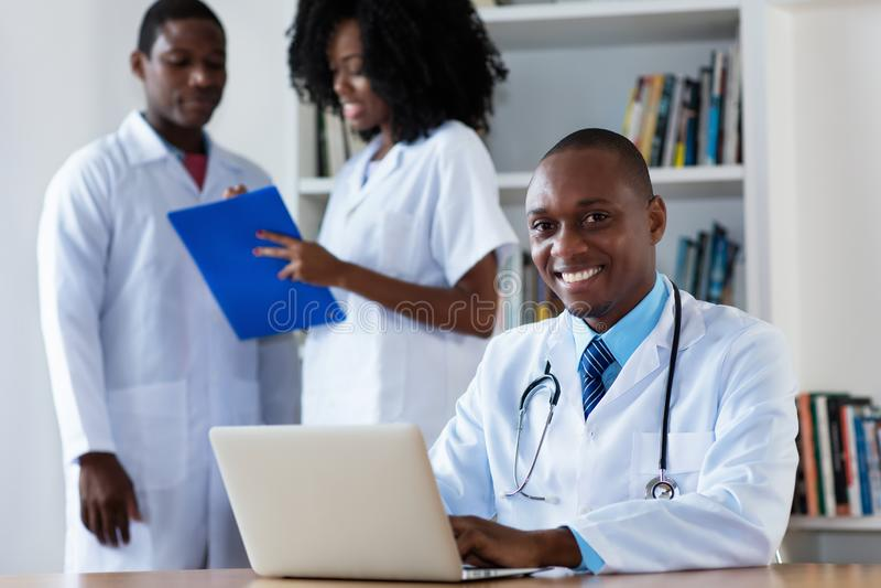 Médecin en chef d'afro-américain avec l'équipe médicale images stock