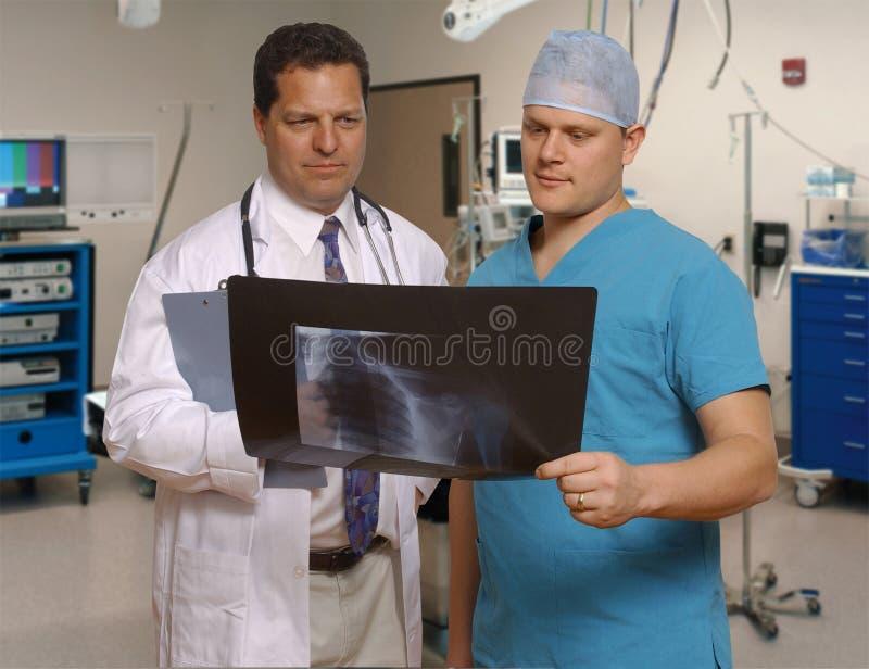 Médecin et chirurgien observant le rayon X image stock