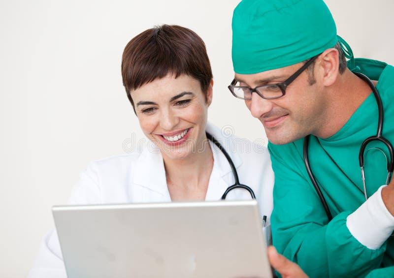 Médecin et chirurgien regardant un ordinateur portatif photo libre de droits
