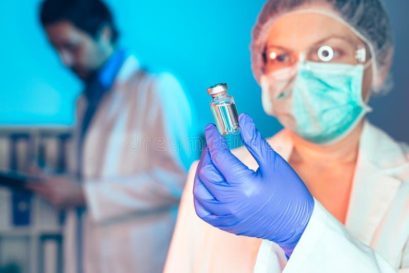 Médecin et infirmière analysant le vaccin inconnu de MMR photographie stock