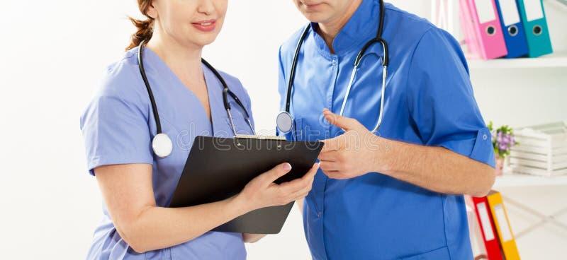 Médecin et infirmière discutant de quelque chose dans la clinique Deux médecins dans un cabinet médical photo de fermeture photographie stock libre de droits