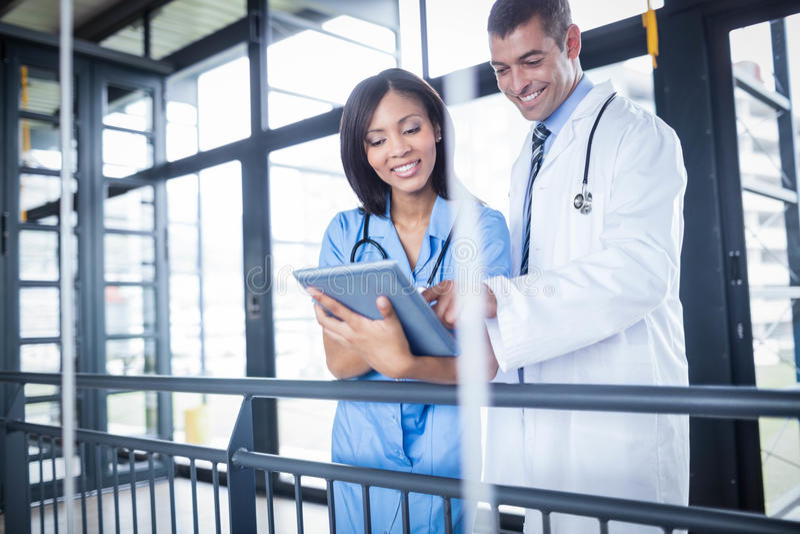 Médecin et infirmière regardant le comprimé images stock