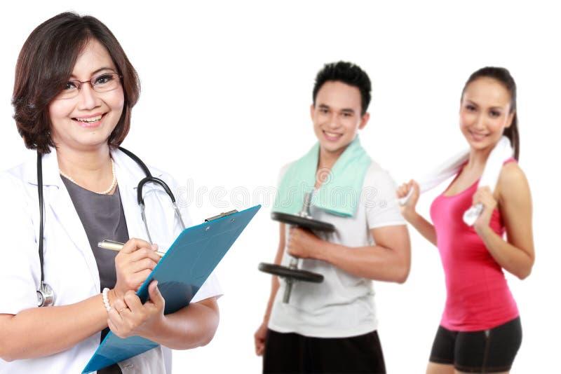 Médecin et les gens faisant l'exercice au fond photo libre de droits