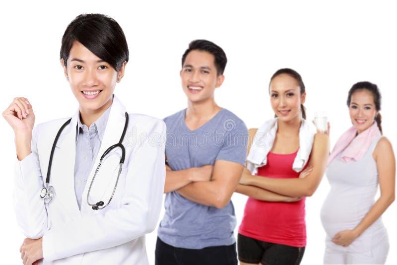 Médecin et personnes occasionnelles faisant l'exercice, femme enceinte photos stock