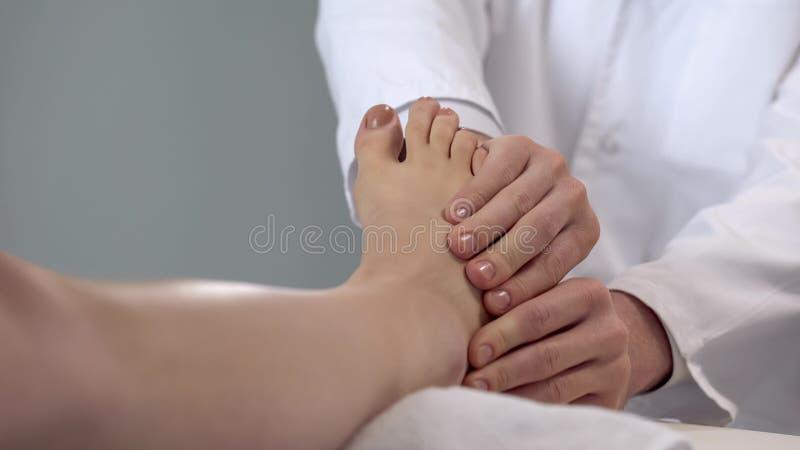 Médecin examinant le pied patient, évaluation de sévérité de blessure, soins de santé photos libres de droits
