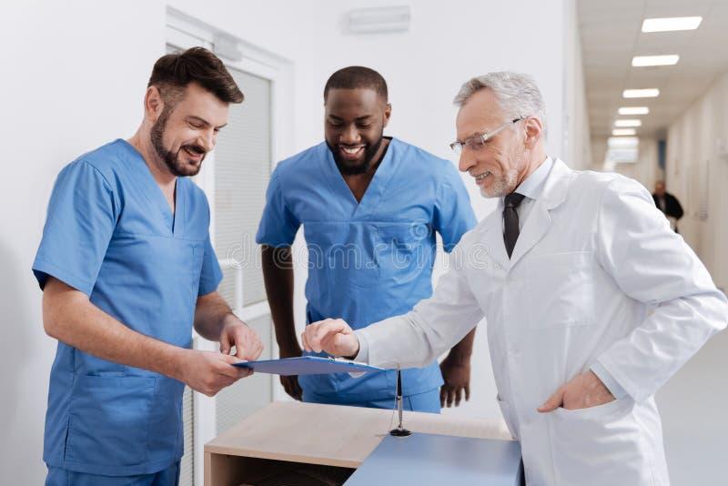 Médecin expérimenté positif vérifiant la qualité du travail dans l'hôpital photos libres de droits