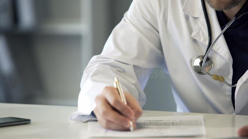 Médecin expérimenté remplissant le formulaire de réclamation d'assurance médicale maladie, soins de santé photos libres de droits