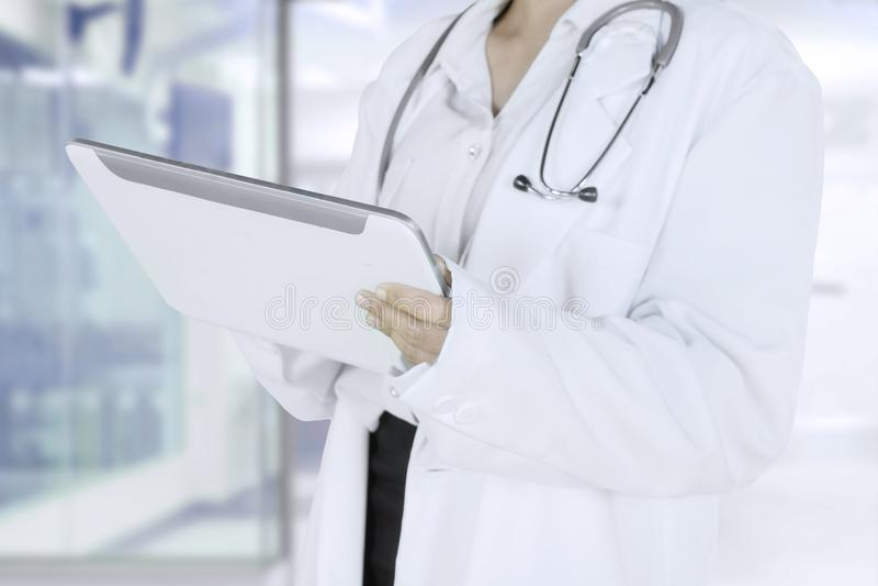 Médecin féminin tenant un comprimé dans la clinique image libre de droits