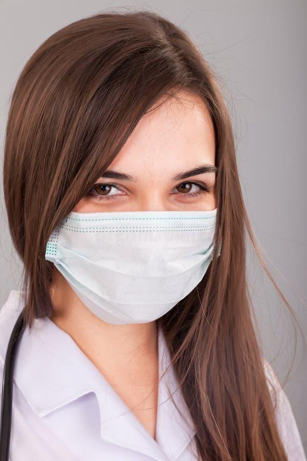 Médecin/infirmière souriant derrière le masque de chirurgien. Portrait de plan rapproché de image stock