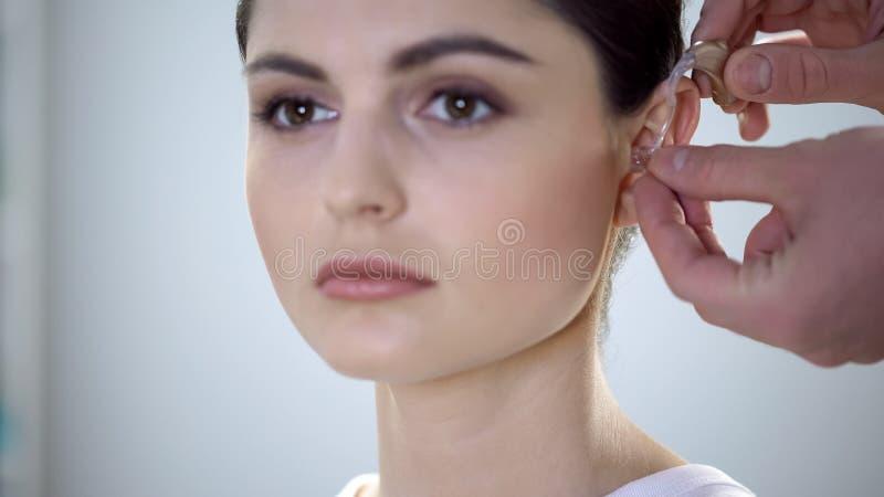 Médecin mettant l'aide sourde sur l'oreille de la jeune femme, traitement d'altération de la perception auditive photographie stock libre de droits