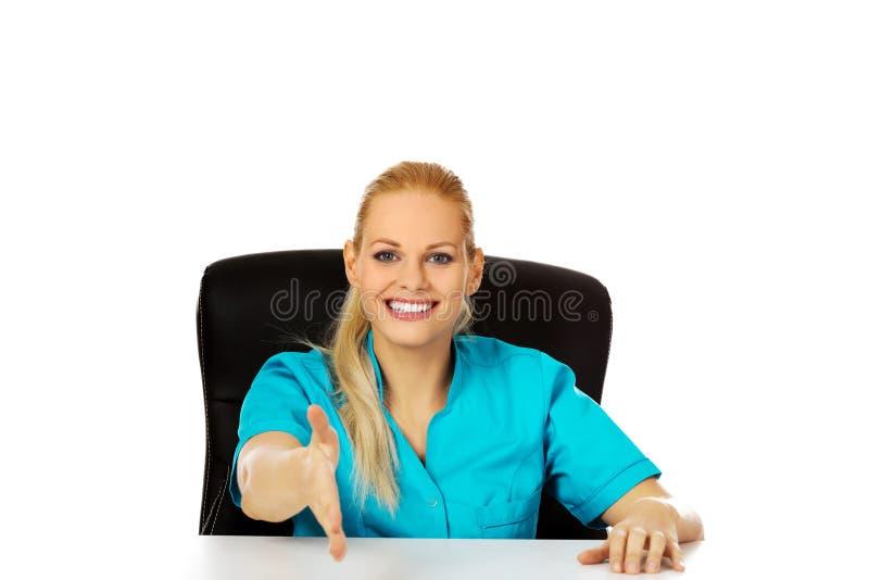 Médecin ou infirmière féminin de sourire s'asseyant derrière le bureau avec la main redy à la poignée de main image libre de droits
