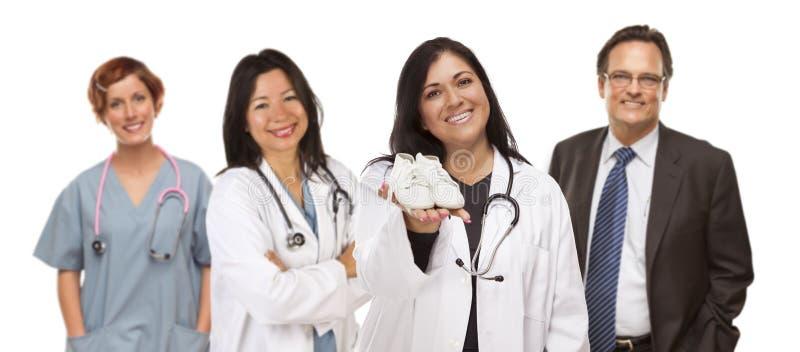 Médecin ou infirmière féminin hispanique avec les chaussures de bébé et l'appui Staf photo libre de droits
