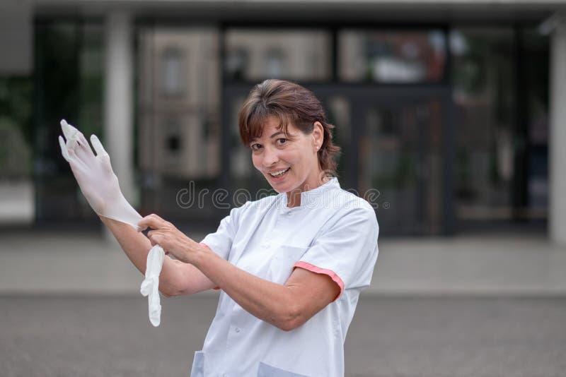 Médecin ou infirmière féminin mettant des gants de latex images libres de droits