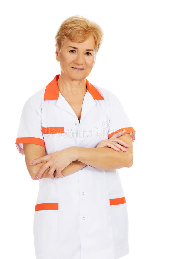 Médecin ou infirmière féminin plus âgé de sourire avec les bras pliés photo stock