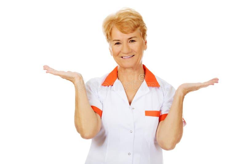 Médecin ou infirmière féminin plus âgé de sourire présent quelque chose sur les paumes ouvertes photos stock