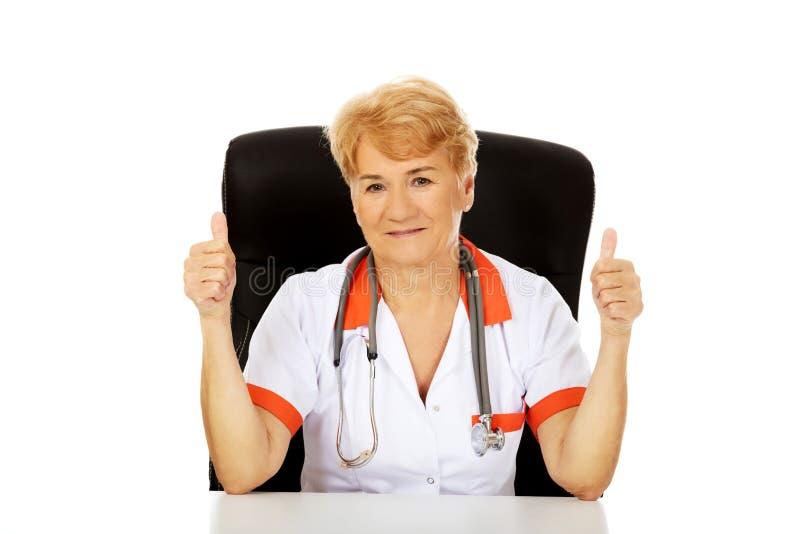 Médecin ou infirmière féminin plus âgé de sourire s'asseyant derrière le bureau et les pouces d'expositions  photographie stock