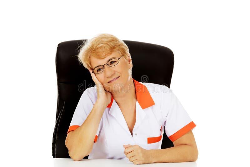 Médecin ou infirmière féminin plus âgé de sourire s'asseyant derrière le bureau se penchant en main photographie stock libre de droits