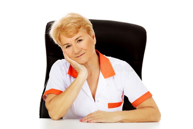 Médecin ou infirmière féminin plus âgé de sourire s'asseyant derrière le bureau se penchant en main photo libre de droits