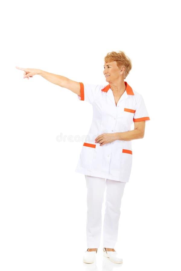 Médecin ou infirmière féminin plus âgé de sourire se dirigeant pour le copyspace ou quelque chose photographie stock