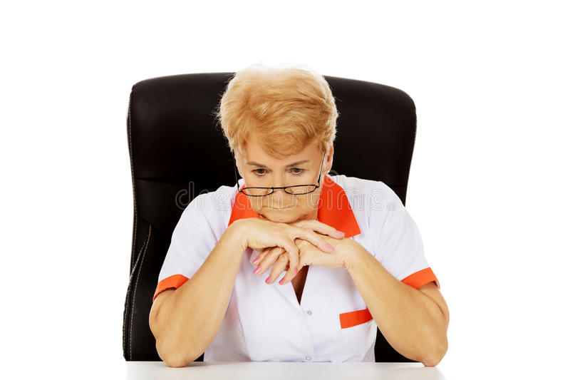 Médecin ou infirmière féminin plus âgé inquiété s'asseyant derrière le bureau photo stock