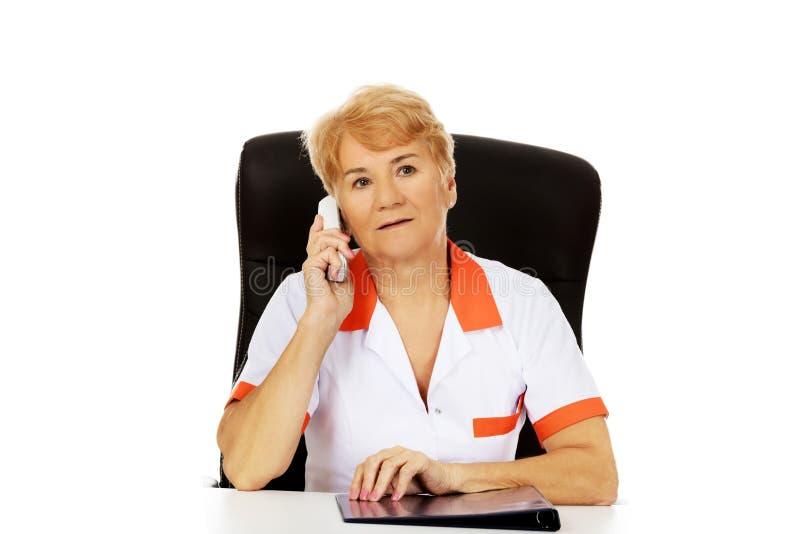 Médecin ou infirmière féminin plus âgé inquiété s'asseyant derrière le bureau et parlant par un téléphone images stock