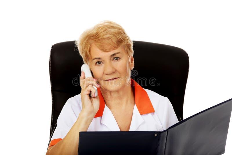 Médecin ou infirmière féminin plus âgé inquiété s'asseyant derrière le bureau et parlant par un téléphone images libres de droits