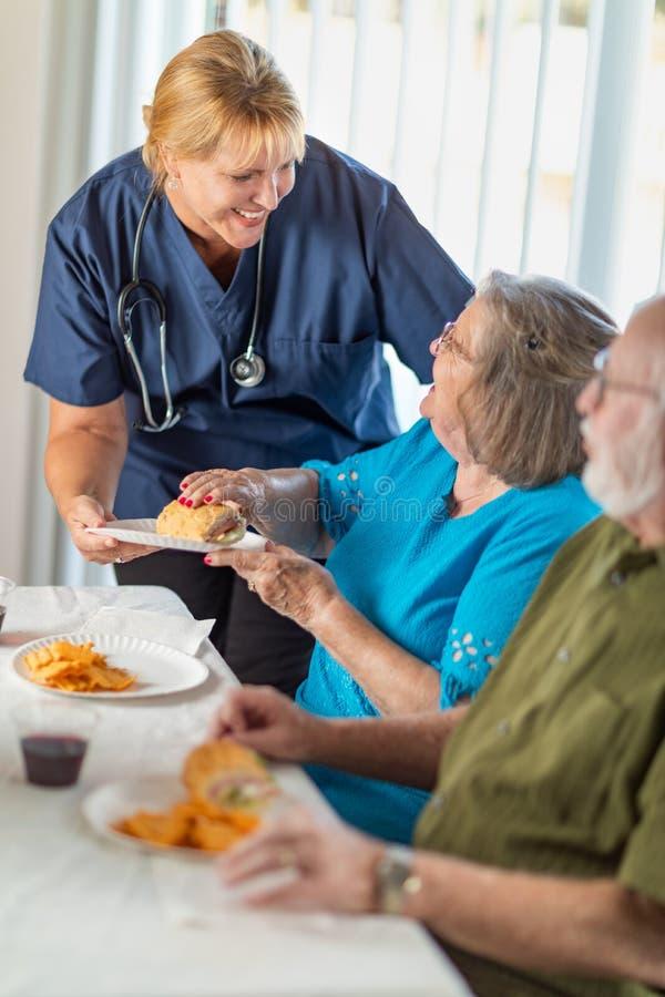 Médecin ou infirmière féminin Serving Senior Adult couplent un repas photos stock