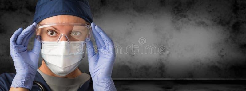 Médecin ou infirmière féminine Wearing Goggles, gants chirurgicaux et masque protecteur contre la bannière foncée sale de fond image stock