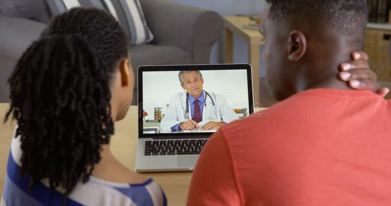Médecin parlant à de jeunes couples noirs au sujet de douleur cervicale au-dessus de la causerie visuelle photos libres de droits