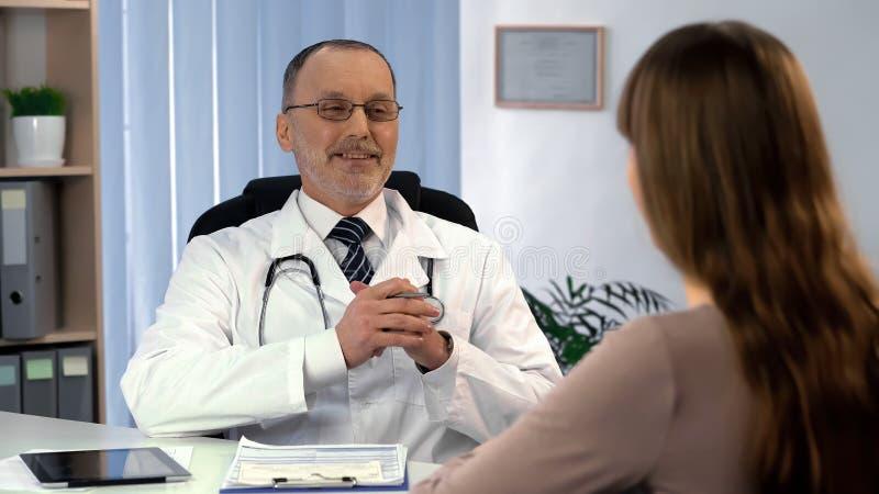 Médecin satisfait du résultat de traitement parlant au patient féminin, récupération images libres de droits