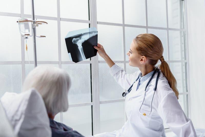 Médecin sortant démontrant l'image au retraité photographie stock