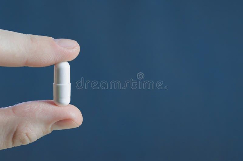 Médecine de capsule de Tablette dans des doigts en gros plan photo stock