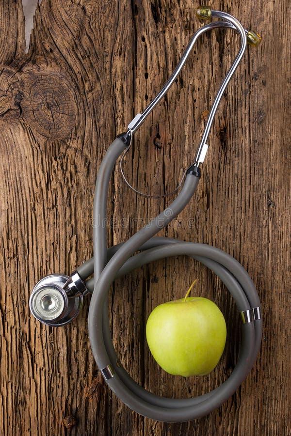 Médecine parallèle - stéthoscope et pomme verte sur la vue supérieure en bois de table Fond médical Concept pour le régime, soins photographie stock