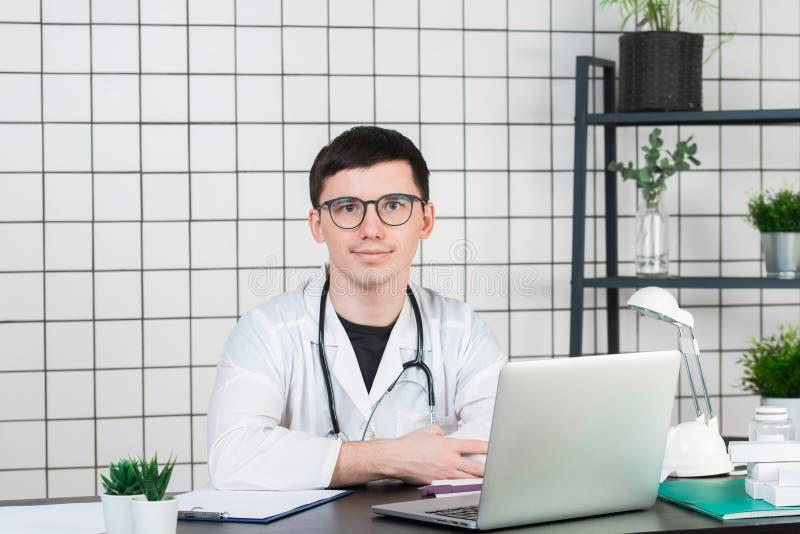 Médecine, profession, technologie et concept de personnes - docteur masculin de sourire avec l'ordinateur portable dans le bureau photographie stock
