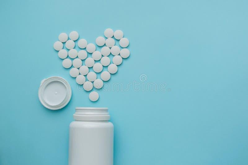 Médecines blanches, pilules en forme de coeur de rond sur le fond bleu photographie stock