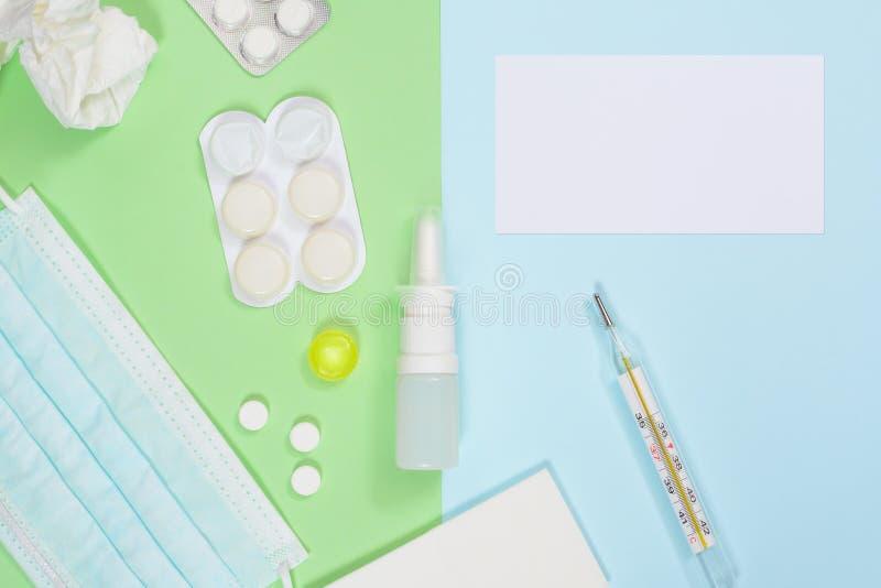Médecines, thermomètre, pulvérisation nasale, mouchoirs, masque médical sur le fond vert-bleu Traitement de froid et de grippe images libres de droits