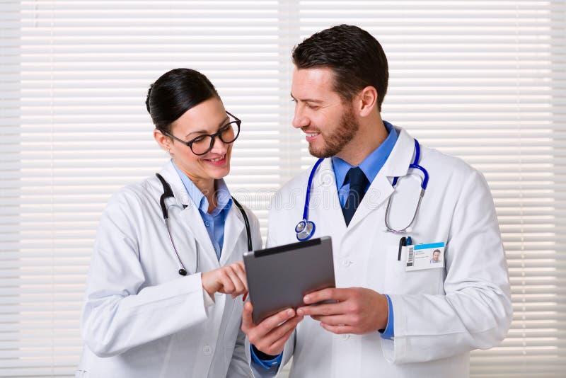 Médecins à l'aide du comprimé au travail photo stock