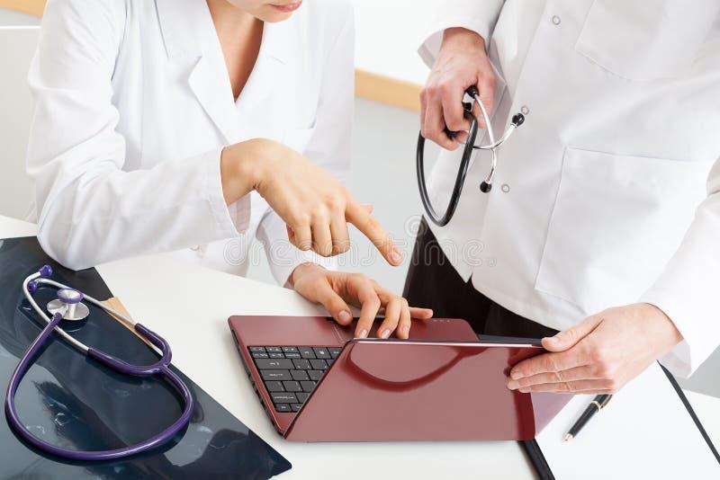 Médecins analysant des documents d'ordinateur photographie stock libre de droits