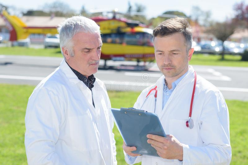 Médecins avec l'hélicoptère médical de presse-papiers à l'arrière-plan photos stock